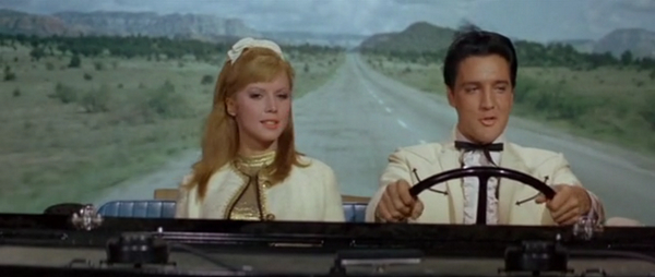 Elvis and friend behind the wheel of a large automobile