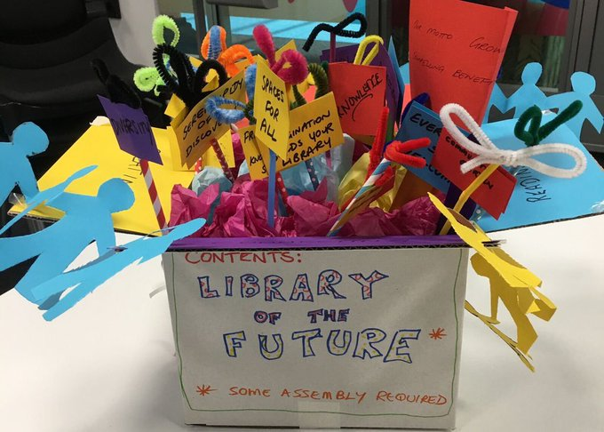 "Box full of colourful characters and figures with placards labelled ""Library of the Future - Some assembly required"