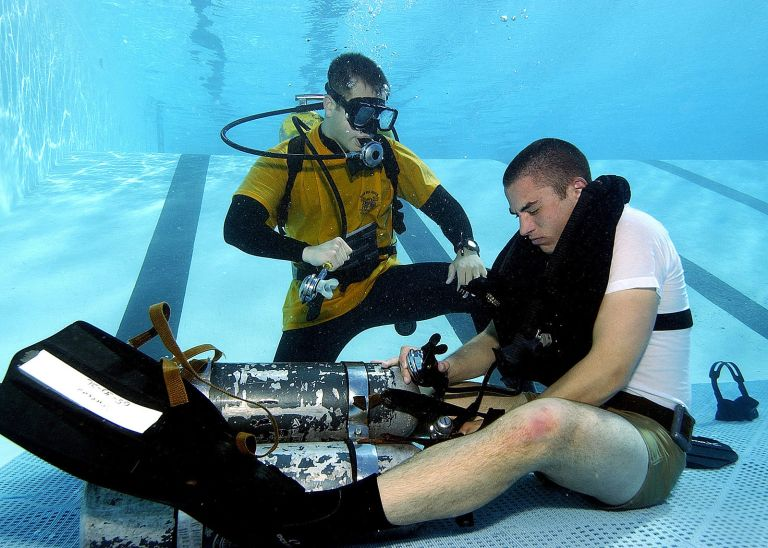 US_Navy_050209-N-3093M-004_Naval_Diving_and_Salvage_Training_Center_instructor_stands_ready_to_offer_assistance_to_a_diver_student_if_he_is_not_able_to_regain_his_own_air_supply_during_a_problem_solving_exercise_at_the_pool_con